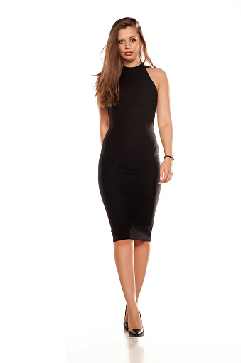 istock young woman in tight black dress walking on white background 641684890