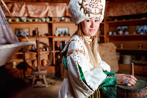 Young woman in traditional yurt dwelling Portrait of a cute young woman in traditional yurt dwelling of Siberian peoples dressed in ethnic attire. mongolian culture stock pictures, royalty-free photos & images
