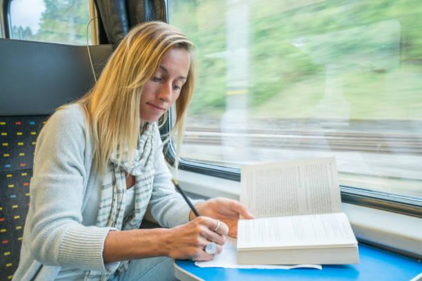 junge frau im zug lesen und studieren, reisen menschen lernkonzept - schweizer bahn weibliche genießen transportmittel - schnell lesen lernen stock-fotos und bilder