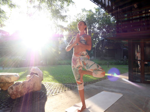 Young woman in tree yoga pose standing in courtyard in sun flare Young woman in tree yoga pose standing in courtyard in sun flare. contributor stock pictures, royalty-free photos & images