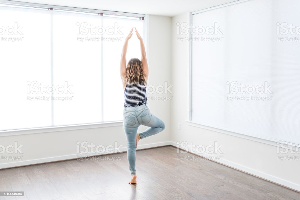Young woman in tree yoga pose standing on one leg in empty modern new...
