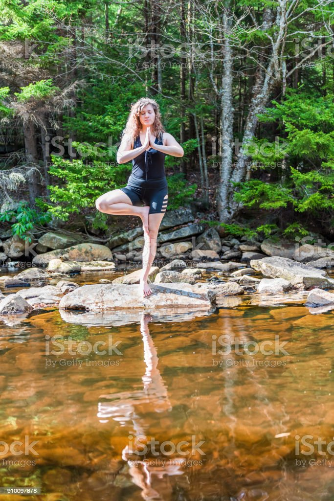Young woman in tree yoga pose standing on one leg on rock by river in...