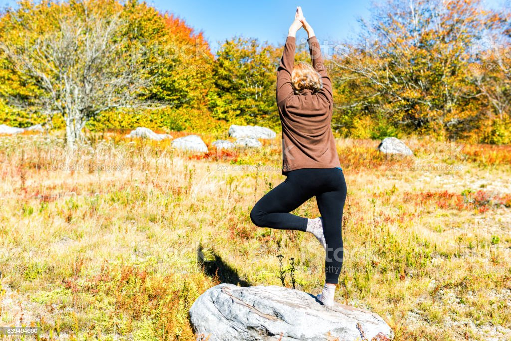 Young woman in tree yoga pose standing on one leg on rock in West...
