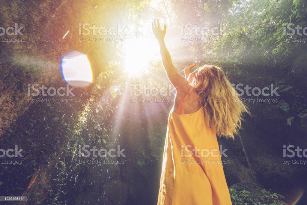 Junge Frau im tropischen Regenwald schönes Licht blickte und die Regentropfen mit Händen zu berühren. Die Leute reisen genießen Natur und Lebenskonzept – Foto