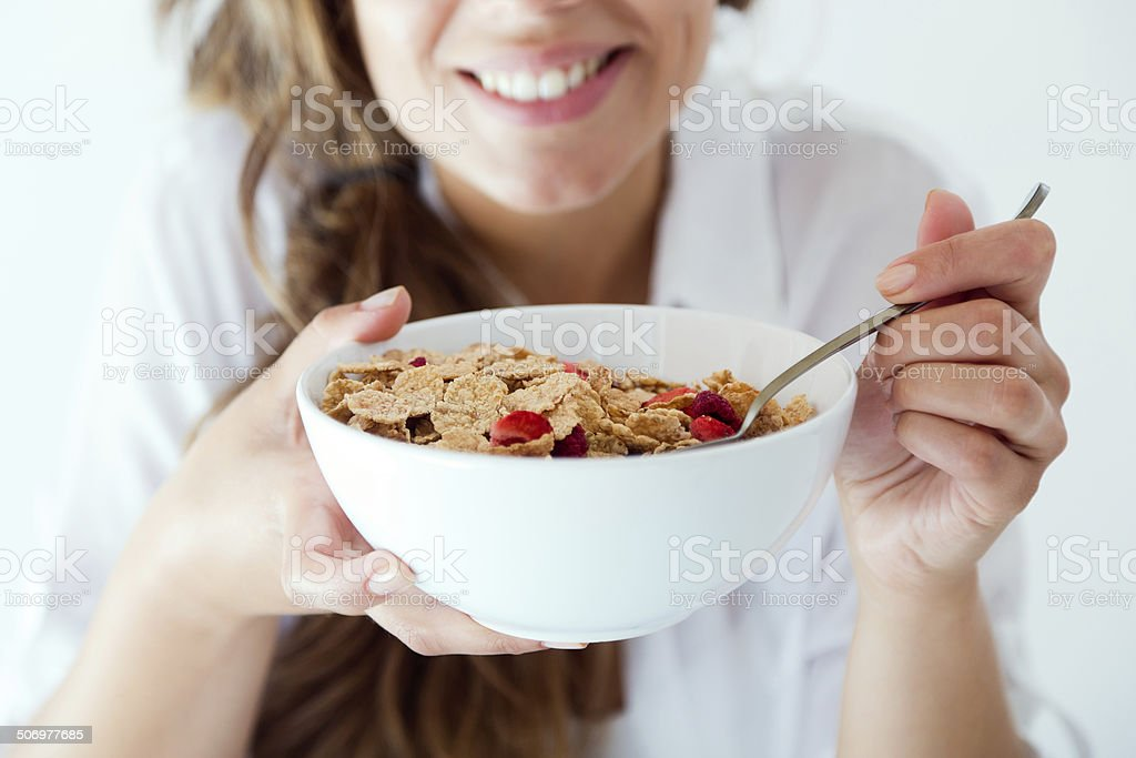 Young woman in underwear eating cereals. Isolated on white. stock photo