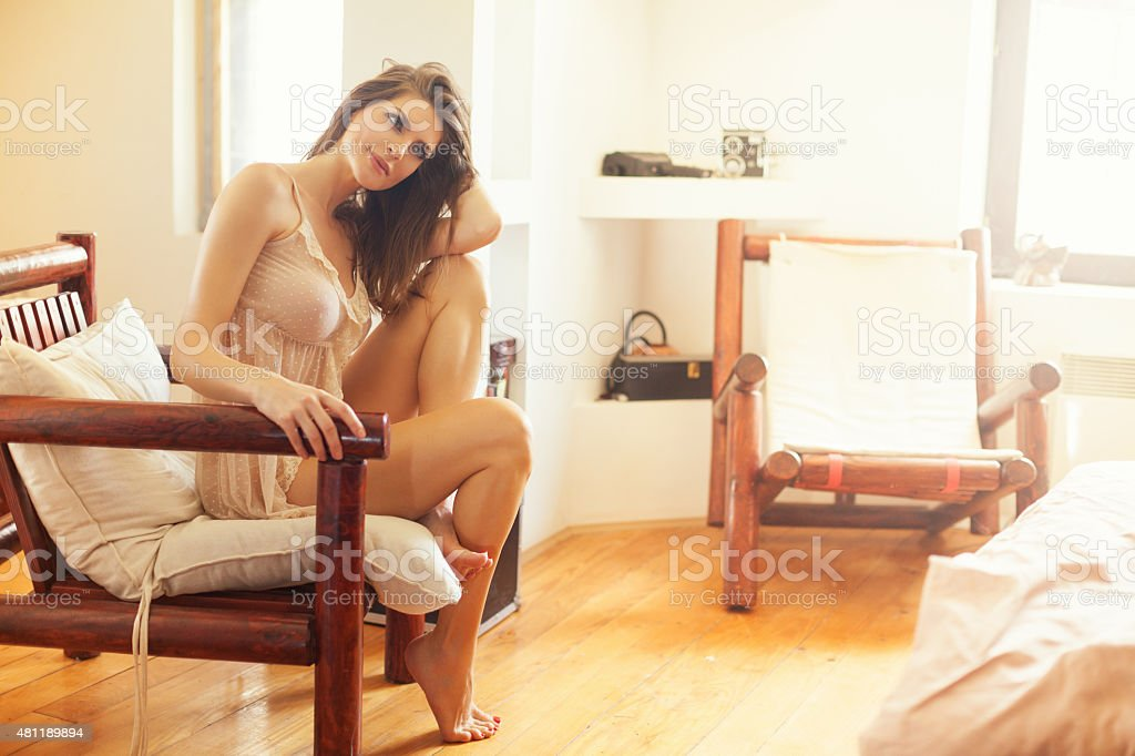 Young woman in underwear sitting next to the window stock photo