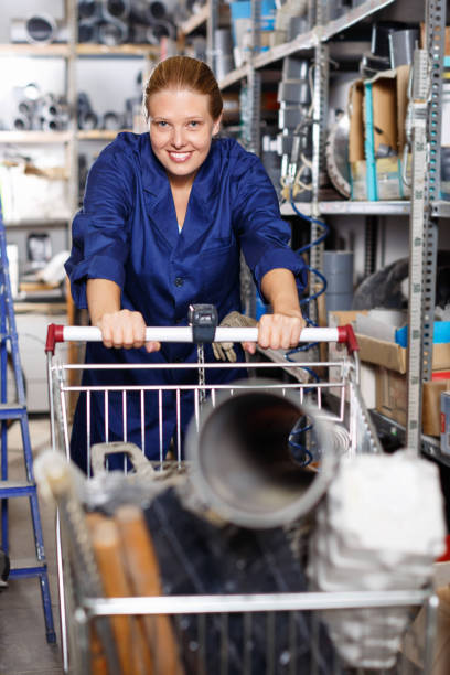 Young woman in uniform walking during shopping construction  materials with  basket in build shop stock photo