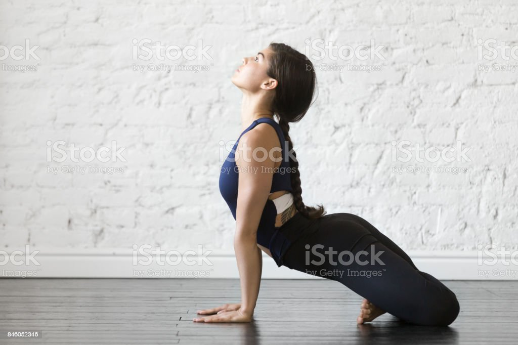 Young woman in upward facing dog with padmasana legs pose stock photo