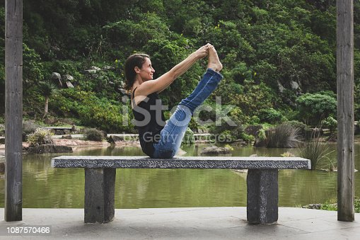 Female yogi in balancing stick pose grabbing toes with hands