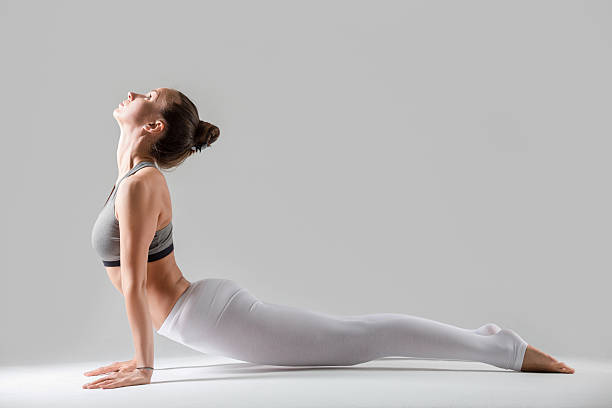 Young woman in Urdhva mukha shvanasana pose, grey studio backgro Young attractive woman practicing yoga, standing in upward facing dog exercise, Urdhva mukha shvanasana pose, working out wearing sportswear, indoor full length, isolated, grey studio background upward facing dog position stock pictures, royalty-free photos & images