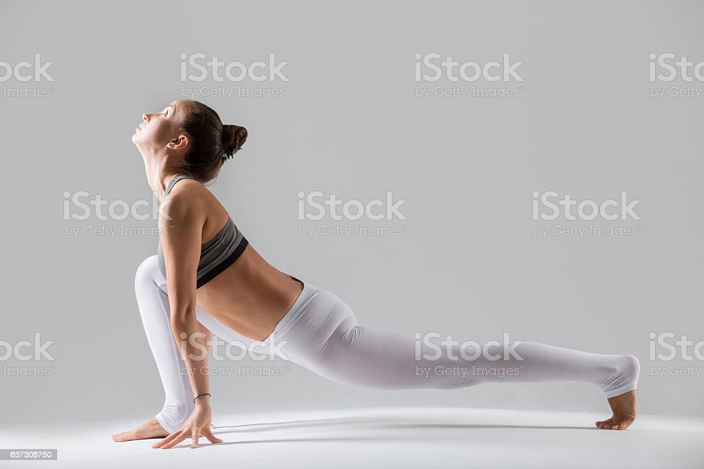 Young woman in Utthan Pristhasana pose, grey studio background stock photo