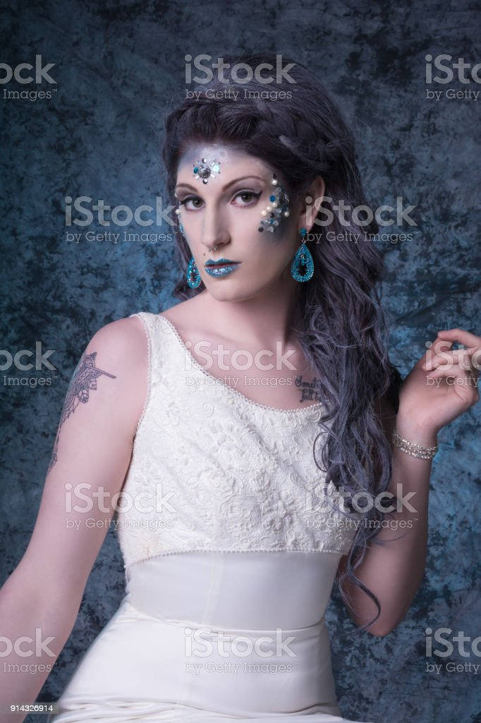 Young woman in wedding dress and jeweled makeup, three quarter length, looking askance at camera stock photo