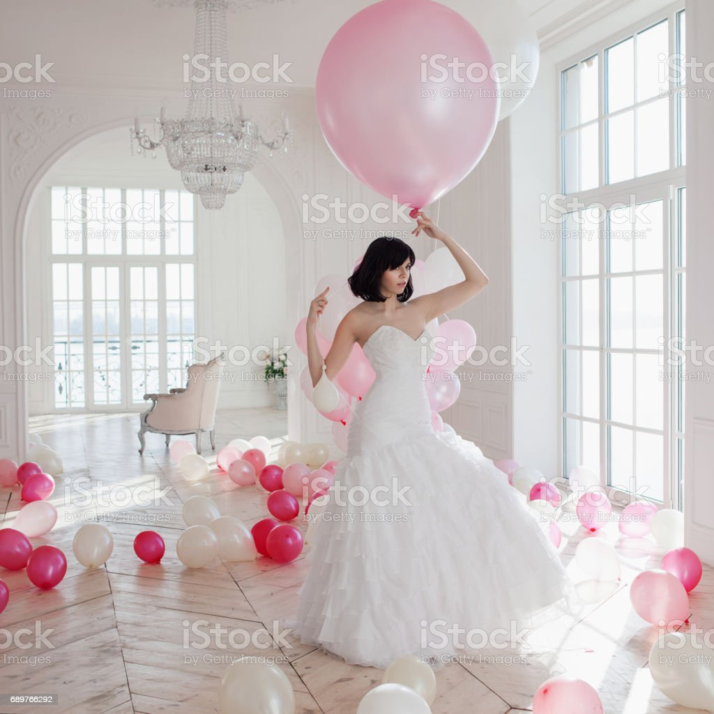 Young woman in wedding dress in luxury interior flies on pink and white balloons. stock photo