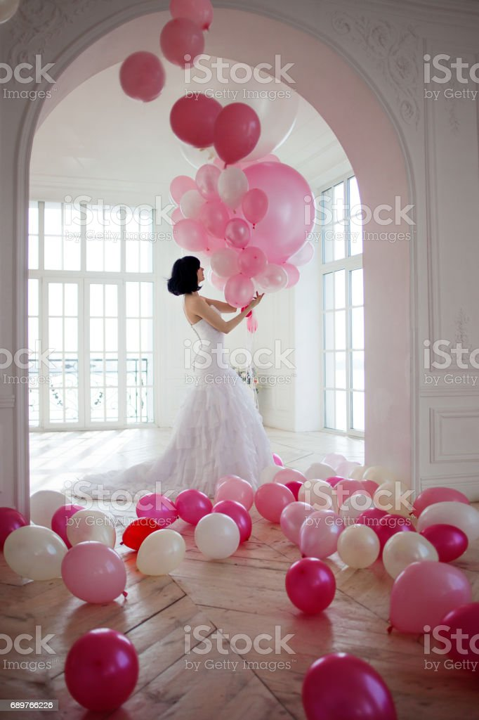 Young woman in wedding dress in luxury interior with a mass of pink and white balloons. stock photo