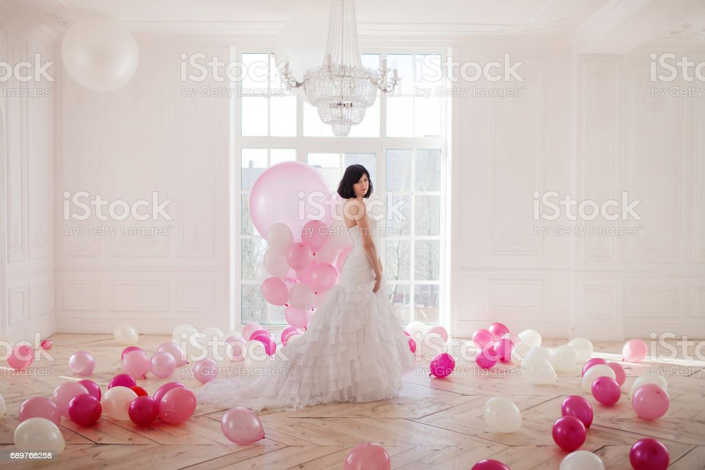 Young woman in wedding dress in luxury interior with a mass of pink and white balloons, standing against the window. stock photo