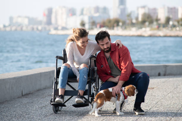 Young woman in wheelchair and boyfriend love the dog stock photo