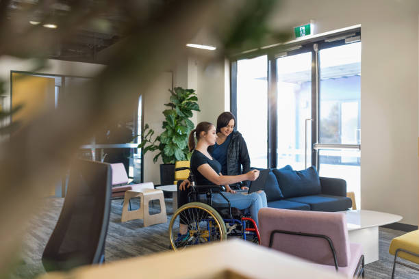 Young Woman In Wheelchair Collaborating With Coworker stock photo