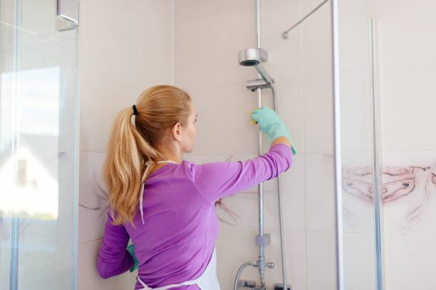 Young woman in white apron cleaning shower stock photo