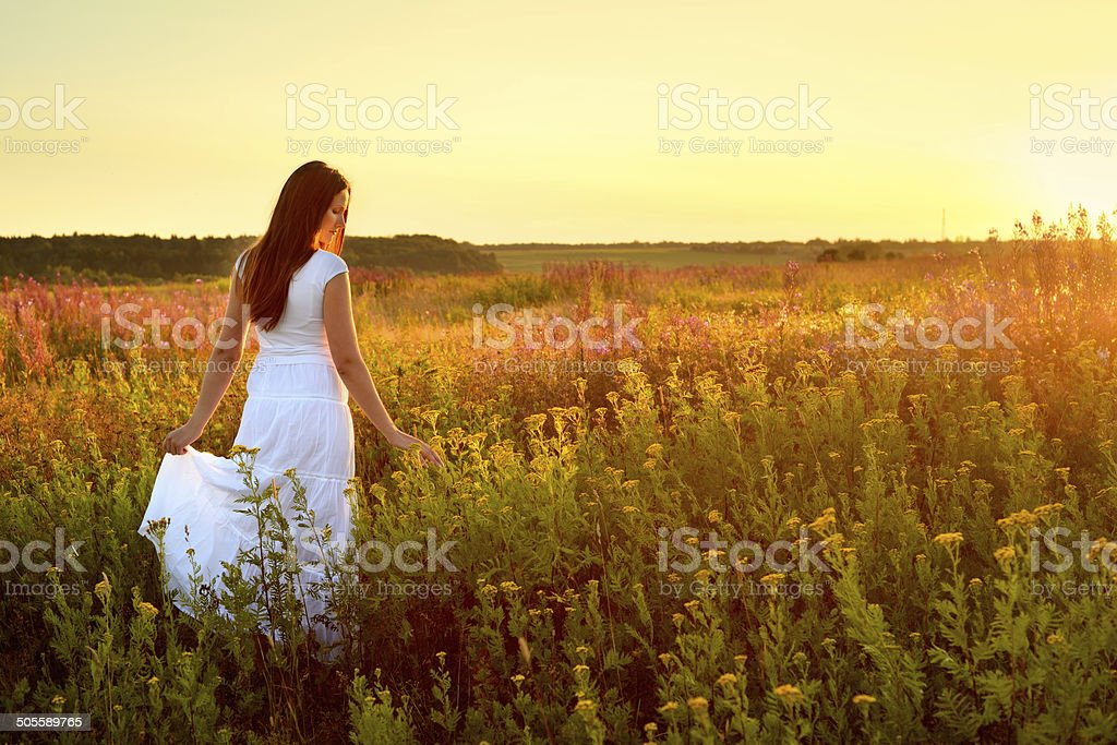Young woman in white clothes standing in field on sunset stock photo