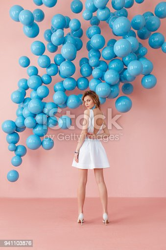 istock Young woman in white cocktail dress standing back to camera on pink wall background with blue bubbles hanging. Dreaming concept. 941103876