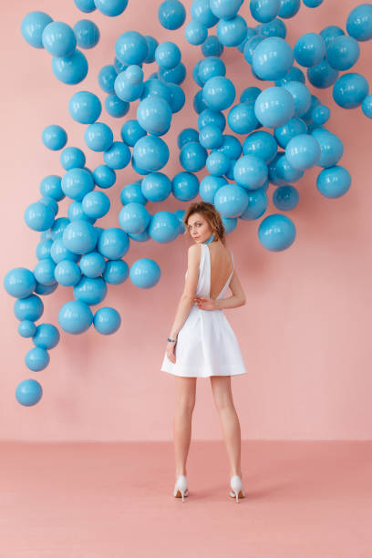 Young woman in white cocktail dress standing back to camera on pink wall background with blue bubbles hanging. Dreaming concept. stock photo