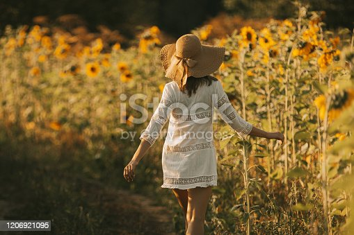 Young woman in white dress and hat goes on the road to the sunset field. Summer vacation concept, recreation in the countryside, nature beauty, gardening.