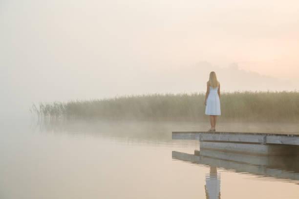 beyaz elbiseli genç kadın yaya köprüsünde tek başına durup göle bakıyor. su üzerinde sis. sisli hava. soğuk sabah. duygusal, ilham verici metin, alıntı veya atasözleri için boş bir yer. geri görünüm. - beyaz elbise stok fotoğraflar ve resimler