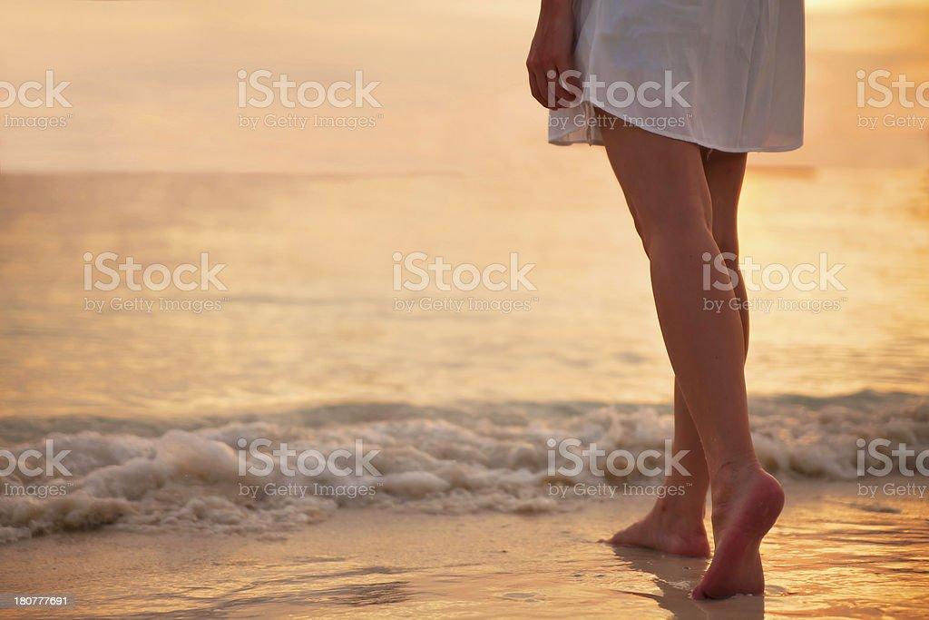 Молодая женщина в белом платье, ходить в одиночку на пляже стоковое фото