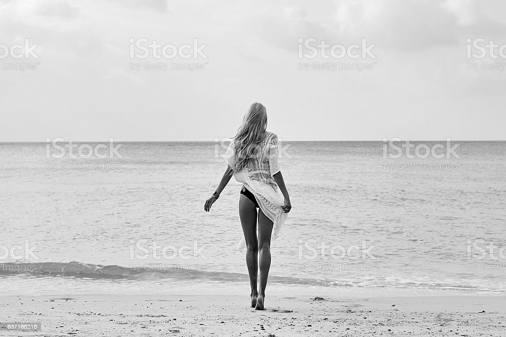 Young woman in white dress walking alone on the beach stock photo