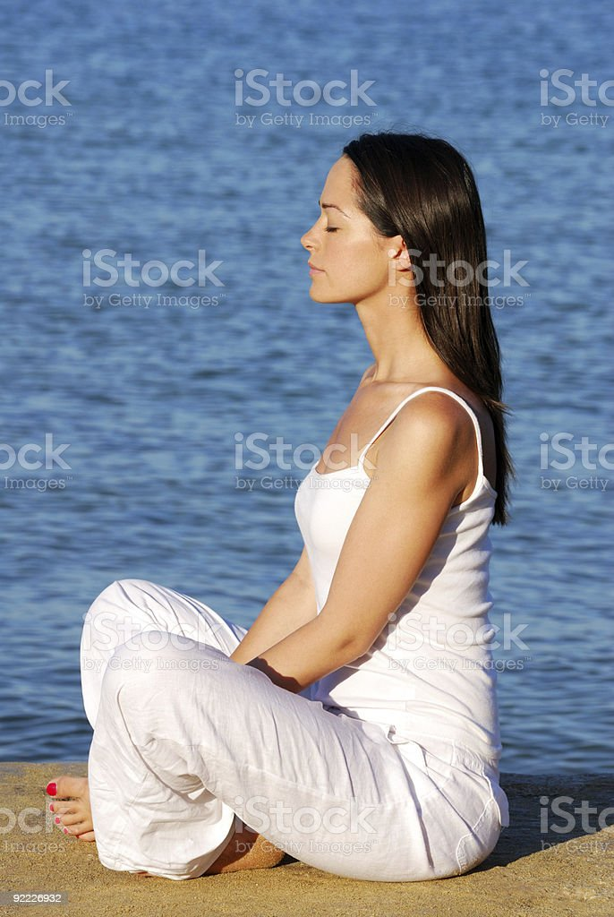 Young woman in white meditating on the beach royalty-free stock photo