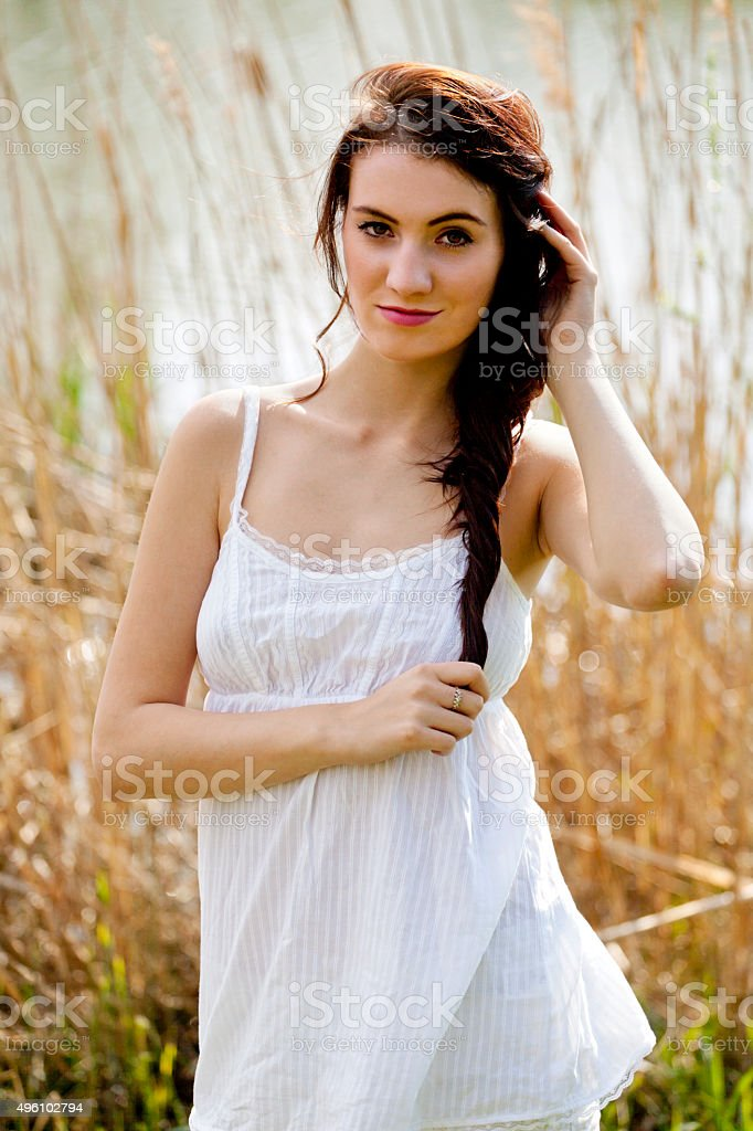 Young woman in white shirt near pond stock photo