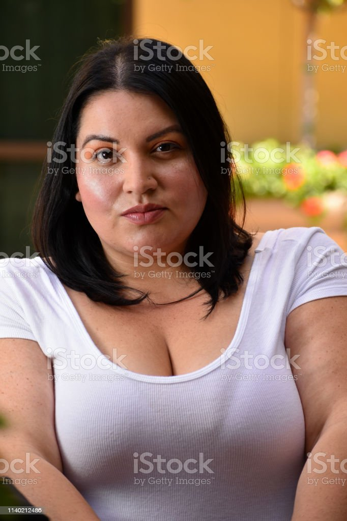 Young Woman in White Shirt with Mouth Closed and Shoulders Up stock photo