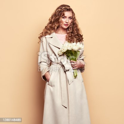 Young elegant woman in trendy white coat. Blonde hair, coral dress, isolated on beige background, studio shot. Fashion spring lookbook. Model woman with white tulips