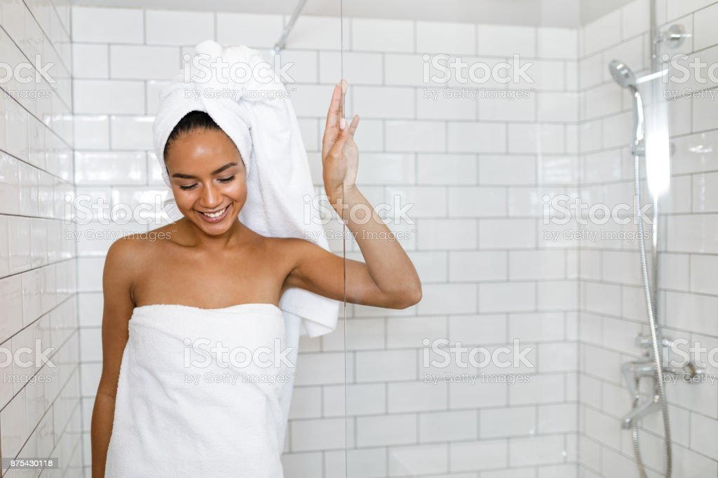 Young woman in white towels wrapped around head and body after shower stock photo