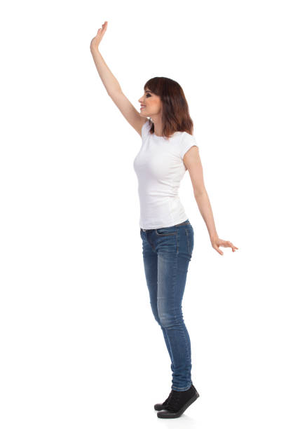 Young Woman In White T-shirt And Jeans Is  Standing TipToe And Waving Hand. Side View. stock photo