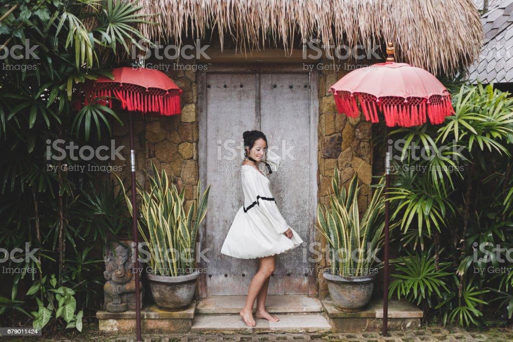 Geleneksel Bali mimarisi ile Ubud köyde beyaz tunik genç kadın. Bali house tarzında. Moda stil, kıvırcık saçlı, ışık elbise. Changgu'da Villa royalty-free stock photo