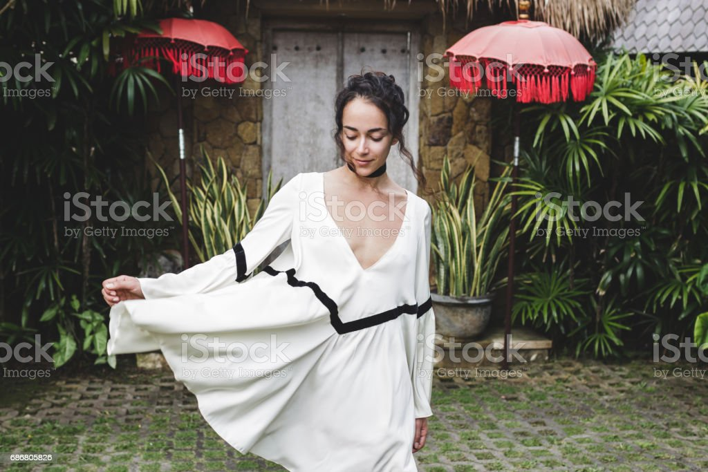Young woman in white tunic in Ubud village with traditional balinese architecture. Style of Bali house. Fashion style, curly hair, light dress. Villa in Changgu stock photo