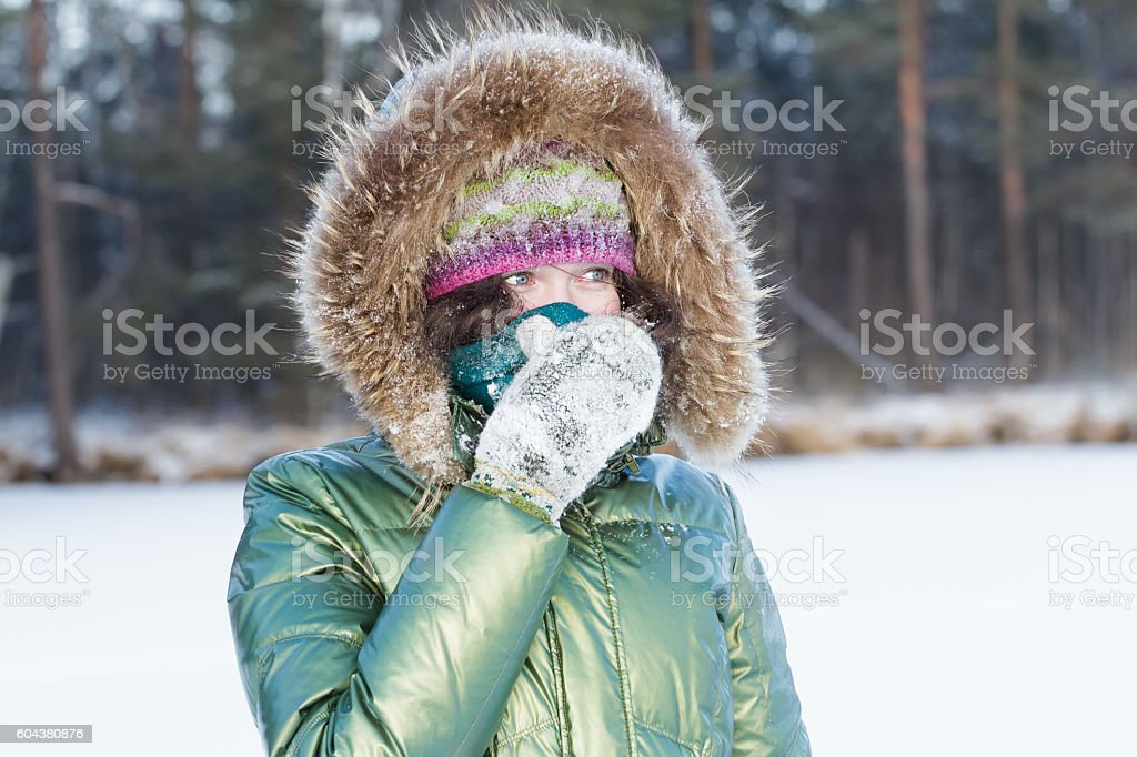 Young woman in winter forest during cold weather hiding face stock photo