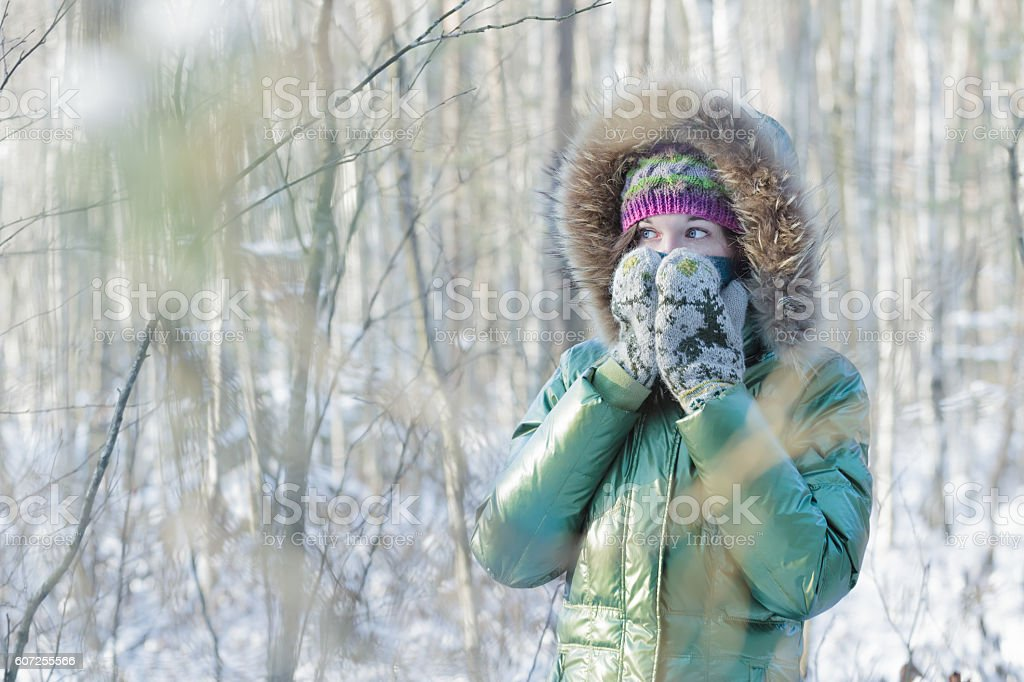 Young woman in winter forest hiding her face in mittens stock photo