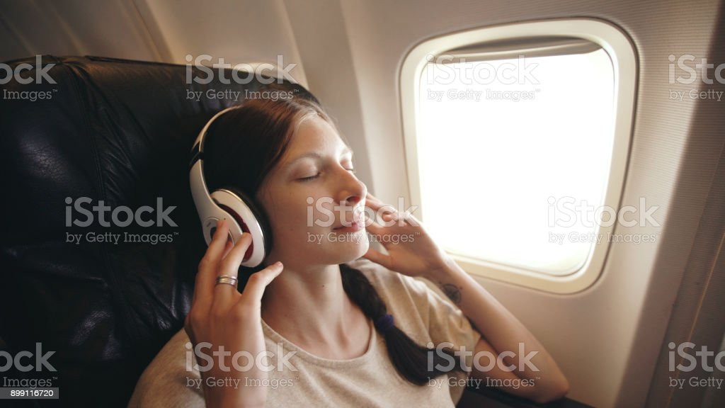 Young woman in wireless headphones listening to music and smiling during fly in airplane stock photo