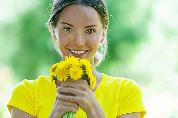 young woman in with bouquet of dandelions stock photo