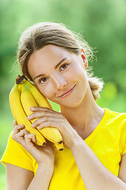 young woman in yellow blouse with banana stock photo
