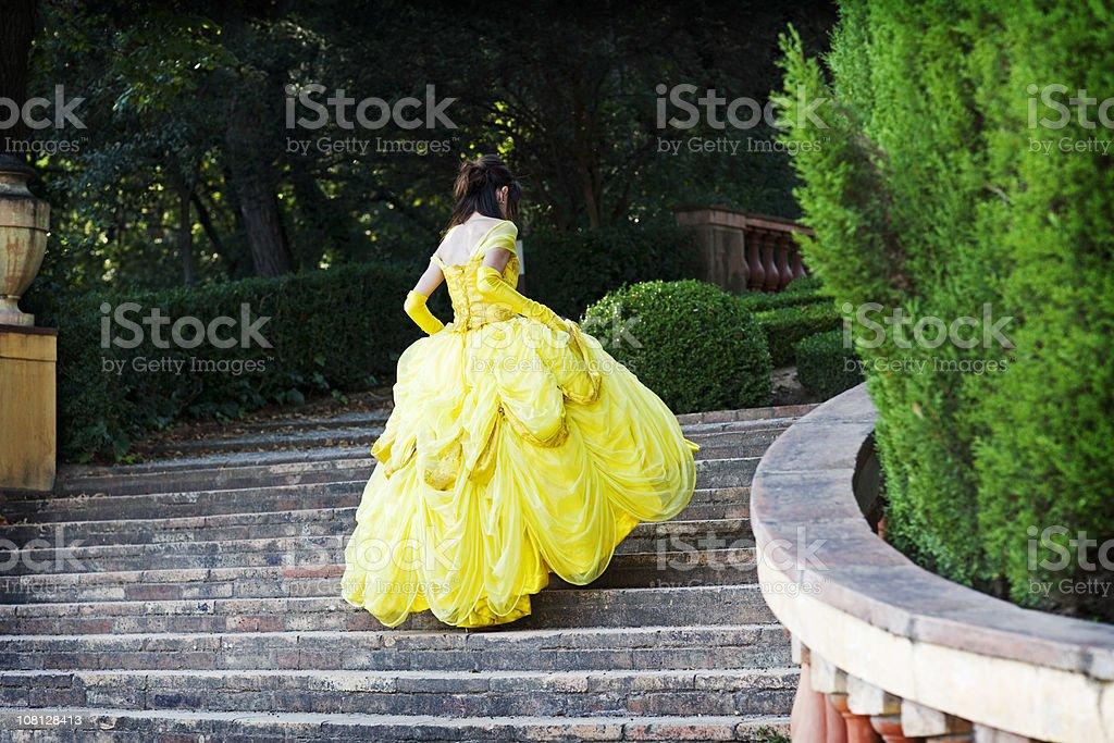 Jeune femme en robe jaune monter les escaliers - Photo