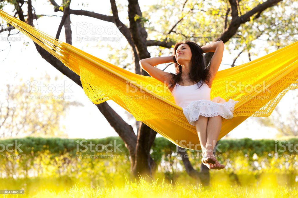 Young woman in yellow hammock in summer park royalty-free stock photo
