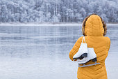 Young woman in yellow jacket and hood staring at ice of lake and holding white skates over shoulder in freezing winter day. Back view of ice skater. Outdoor activities on weekends in cold weather.
