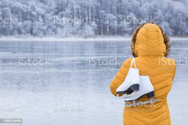 Photo of Young woman in yellow jacket and hood staring at ice of lake and holding white skates over shoulder in freezing winter day. Back view of ice skater. Outdoor activities on weekends in cold weather.