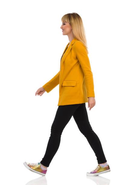 jonge vrouw in gele jas en sneakers is wandelen. zijaanzicht. - zwarte spijkerbroek stockfoto's en -beelden