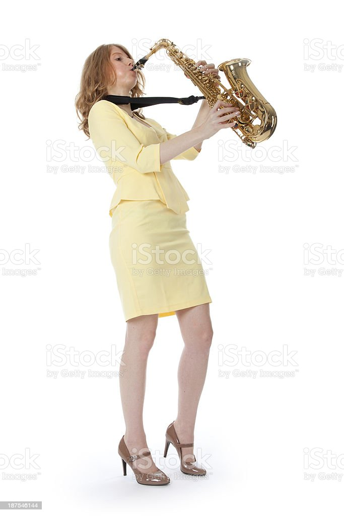 young woman in yellow mini dress playing the alto saxophone stock photo