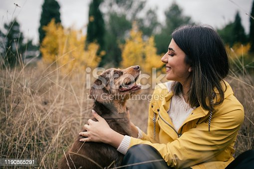 istock young woman in yellow raincoat enjoying time with her old dog in the forest 1190865291