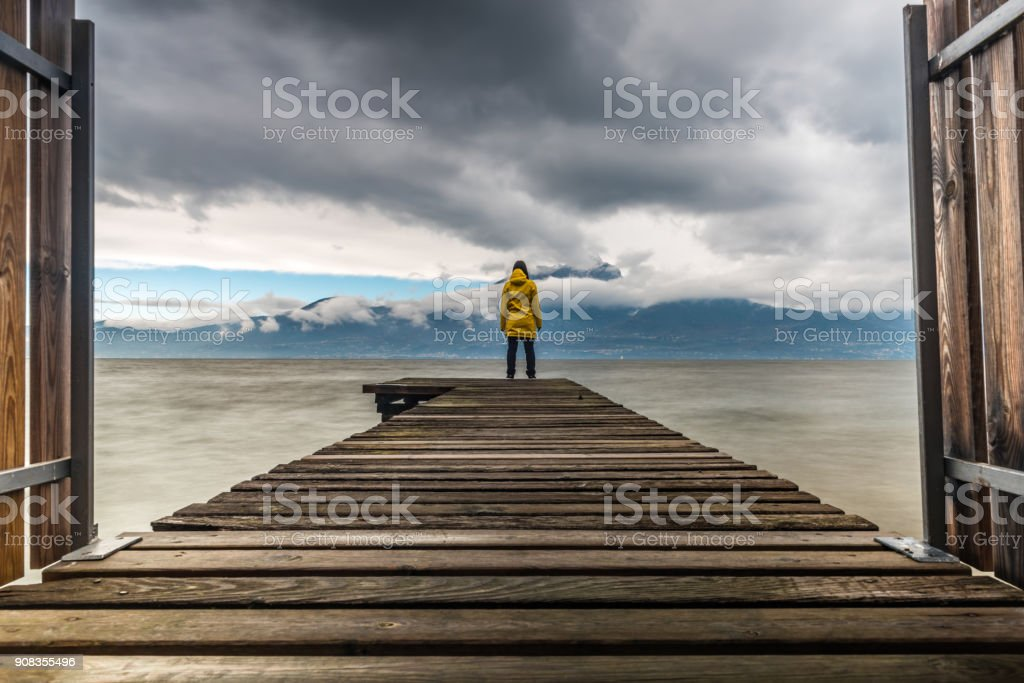 Young woman, in yellow raincoat seen from back at lake stock photo